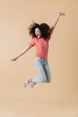 Woman jumping isolated over beige wall background.