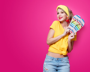 Young redhead girl in yellow t-shirt and blue jeans holding a summer flip flops sandals on pink background.