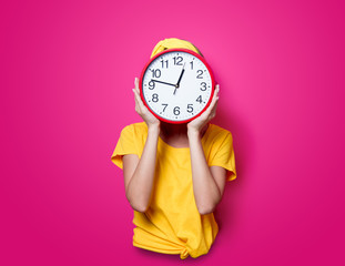 Girl in yellow t-shirt with little blackboard on pink background