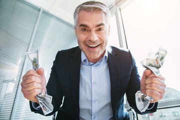 My inspiration. Immoral grey-haired man smiling and holding a lot of money