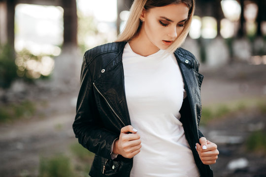 Girl wearing t-shirt and leather jacket posing against street , urban clothing style. Street photography