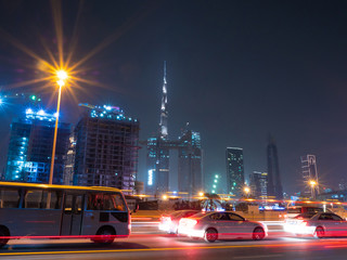 Dubai skyscrapers at night with road traffic late at night.