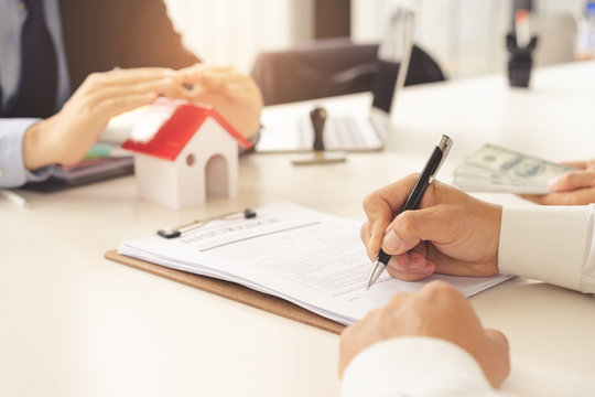 A couple reading and signing contract home insurance at meeting with real estate agent.