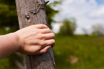 a man wants to jump over a fence in the field. closeup view of the hand. the hand holds onto the fence in the meadow. checks whether a strong fence. stop to rest
