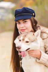 Woman hugging husky dog with stuck out tongue. Close up portrait