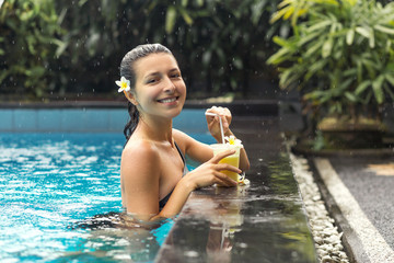 Woman with fuit drink in pool