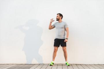 Tired sportsman drinking water