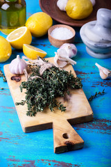 Fresh  thyme, lemons and garlic on wooden board