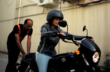 Hanan Iskandar rides a bike as she is assisted by her instructor during her advance bike-riding training at Harley Davidson dealer in Al Khobar, Saudi Arabia,