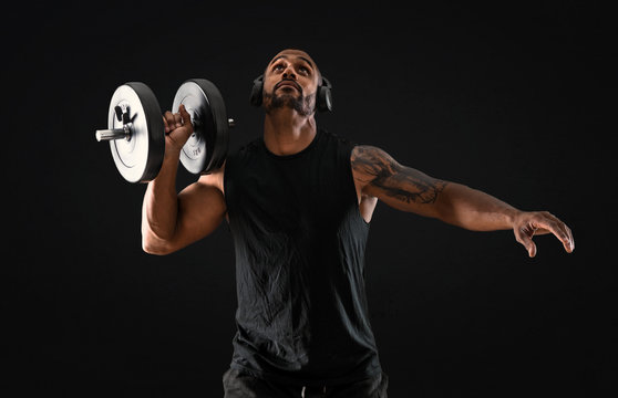 Strong handsome sport man making weightlifting, listening music and  exercising the shoulders on isolated black background