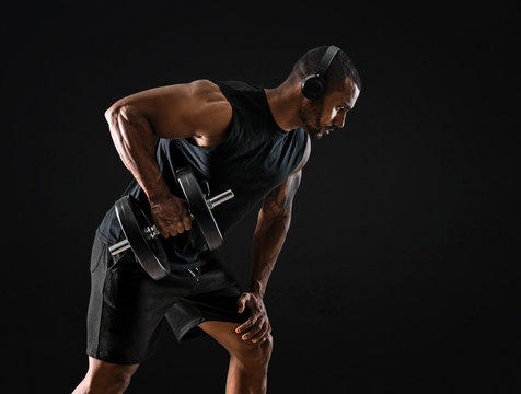 Strong handsome sport man making weightlifting and listening music on isolated black background