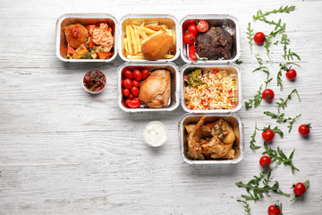 Containers with delicious food on wooden table. Delivery service