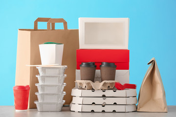 Different packages on table against color background. Food delivery service