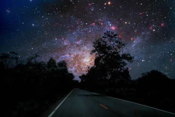 Galaxy on night sky over country road