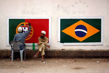 Soccer fans chat as one of them paints the flags of Portugal and Brazil on the wall, ahead of the FIFA World Cup Russia, in Karachi
