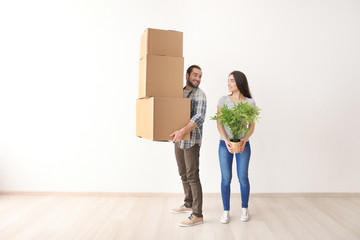 Young couple with boxes and houseplant indoors. Moving into new house
