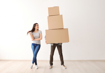 Young couple with boxes indoors. Moving into new house