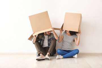 Young couple playing with boxes indoors. Moving into new house