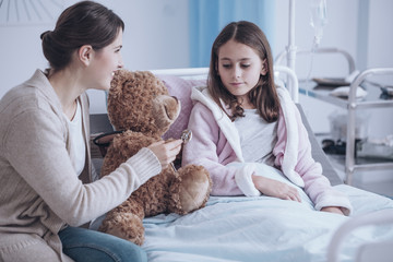 Smiling mother and weak daughter taking care of teddy bear in the hospital