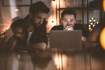 Focused men sitting in front of a laptop at night. Photo with flare