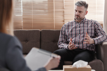 Handsome man gesticulating while talking to his psychologist during a therapy