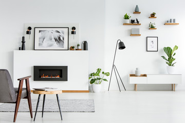 Grey armchair next to table in scandi living room interior with black fireplace and poster. Real photo