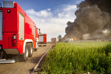 Red fire truck in action with landfill fire in background