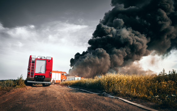 Red fire truck in action with field fire in background