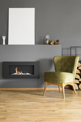 Mockup of white empty poster above fireplace in grey apartment interior with green chair. Real photo