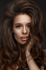 Beautiful brunette model with volume curls, classic makeup and sexy lips. The beauty of the face. Portrait shot in the studio.
