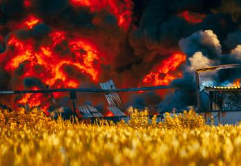 Landfill fire among fields and huge black smoke cloud