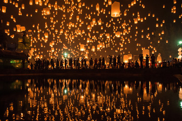numerous lanterns in the sky with reflection, yeepeng lantern festival , Chiangmai, Thailand