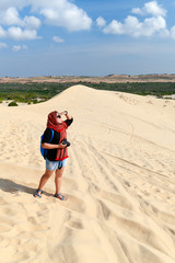 traveler holding camera at white sand dune desert