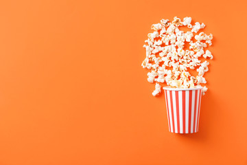 Paper bucket with scattered tasty popcorn on color background Fototapete
