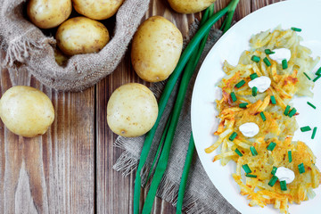 Fried potato pancakes or draniki with sour cream and green onion. The national dish of Belarus, Ukraine and Russia.