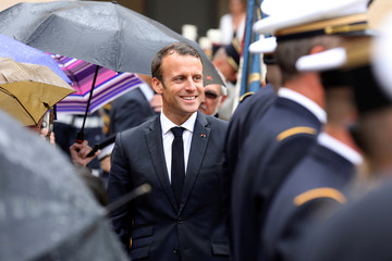 """French President Emmanuel Macron greets guests as he attends the """"prise d'armes"""" military ceremony at the Invalides in Paris"""