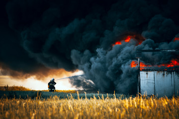 Dramatic scene. Alone firefighter against huge fire with black smoke