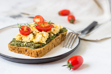 Scrambled eggs on whole wheat bread with avocado and cherry tomatoes
