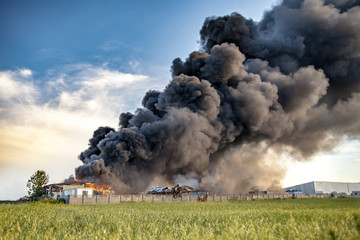 Building fire among fields and huge black smoke cloud