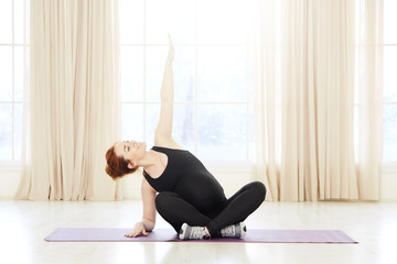 Young pregnant yoga woman working out near windows