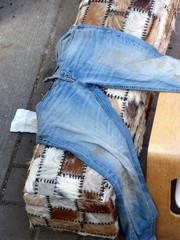 Blaue Jeans mit Schmutzflecken auf einer mit Fell bezogenen Bank an den St. Pauli Landungsbrücken am Hafen in der Hansestadt Hamburg