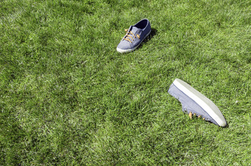 pair of sneakers taken off in a park green grass lawn. Top view angle