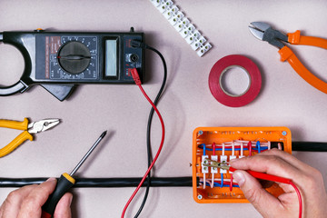 Electrical Engineer adjusts electrical equipment with a multimeter tester in his hand closeup.Electrical repair concept.