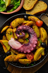 Galician octopus. Octopus with fried potatoes in a clay plate. Pulpo a feira. Spanish.