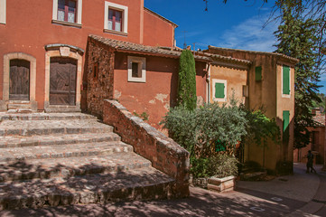 View of traditional colorful house in ocher and staircase, in the historic Roussillon. Located in the Vaucluse department, Provence region, southeastern France.