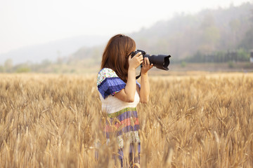 Lady photographer is on rice paddy field while traveling.