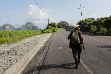 A resident walks along a road as the Fuego volcano spews out a plume of ash and smoke as seen from El Rodeo in Escuintla