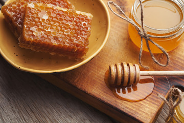 Golden honeycombs and honey jar, closeup