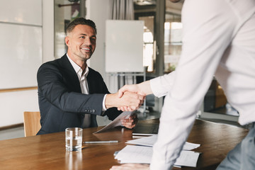 Business, career and placement concept - satisfied director man 30s smiling and shaking hands with male candidate, who was recruited during interview in office