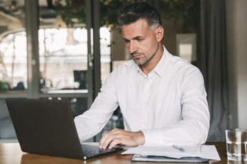 Image of concentrated confident businessman 30s wearing white shirt sitting at table in office, during work with documents and laptop
